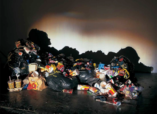 Woman lying down made from trash shadows