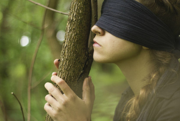 Woman blindfolded holding a tree