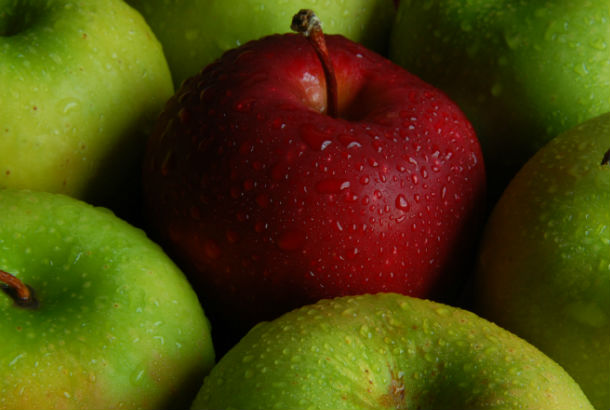 Bright Red apple surrounded by green apples
