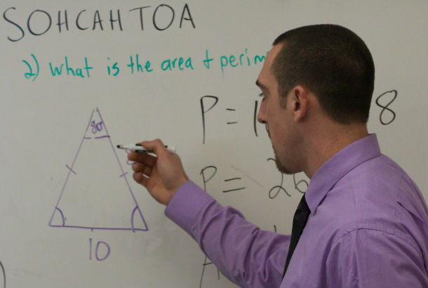 Man standing in front of white board teaching math