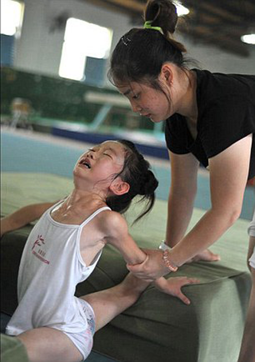 Young Chinese gymnast being stretched