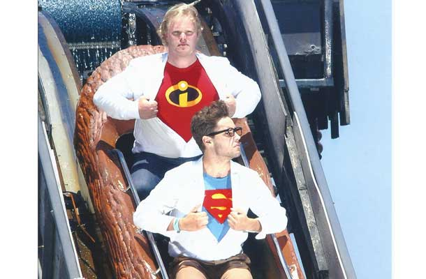 two brothers with superhero logos under shirt