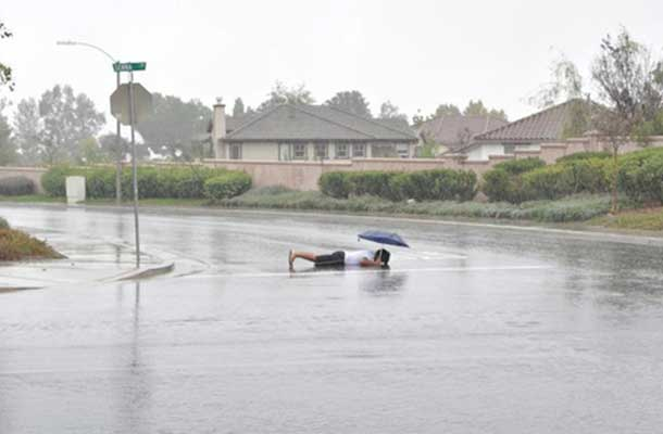 planking in the middle of the street, in the rain, holding an umbrella