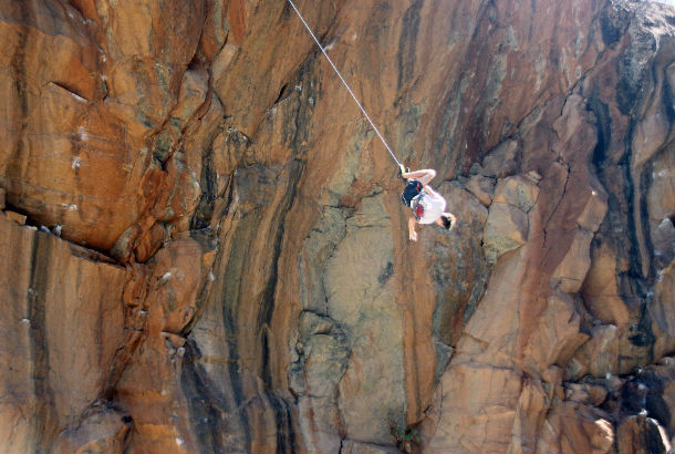 Man upside down midway down a cliffface