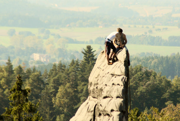 two people on top of a rock face jutting out from mountain overlooking a forest