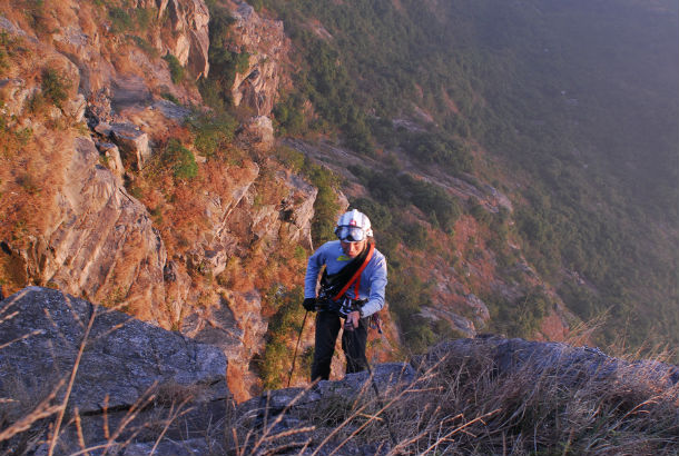 Woman ascending to the top of a mountain
