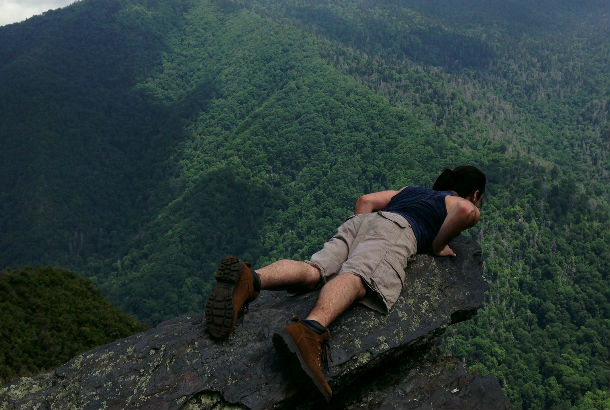 man laying flat on rock looking over valley