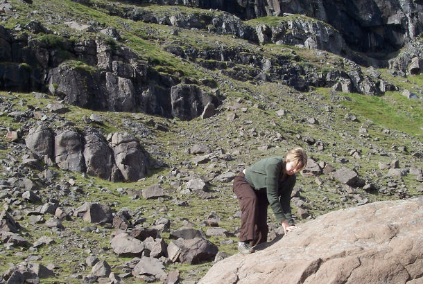 Woman climbing up side of large boulder with her bare hands