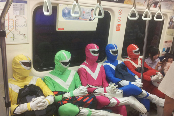 five people dressed as power rangers sit in a row