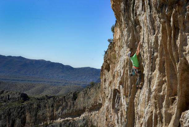 climber climbing rockface with mountains in background