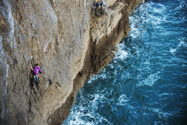 two climbers climbing from the ocean