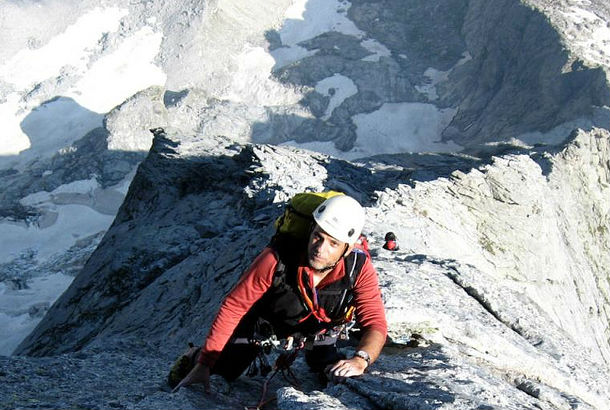 man in gear climbing up side of mountain
