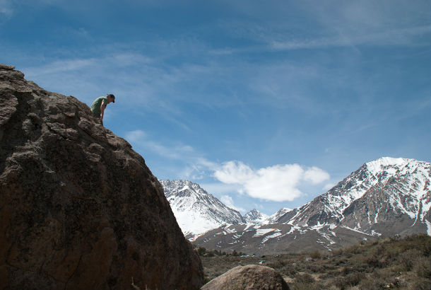 man sitting on top of mountain with snowcapped peak in background
