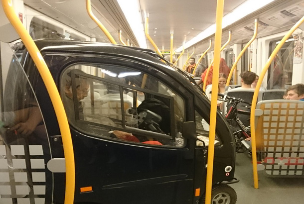 small black car with person inside in subway