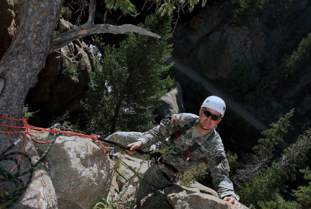 Man in camouflage ties onto tree and begins decent down the mountain