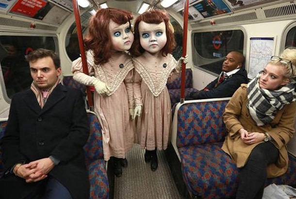 two twin girls in costumes with large heads (like twins in the shining)