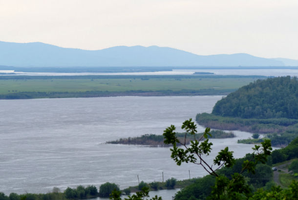 The Amur river from the bank with mountains in the distance