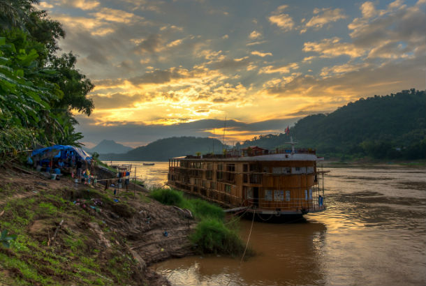 The Mekong River from one bank at sunset with small ferry docked at shore