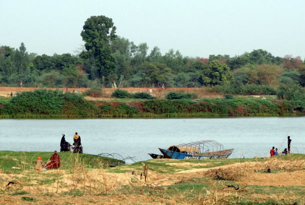 Niger river with boat and people in foreground and trees in background