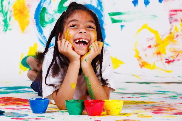 girl covered in paint laughing