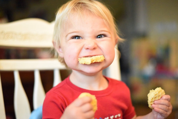 kid laughing and eating