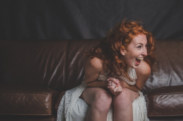 redhead girl laughing on couch