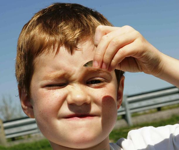 commons.wikimedia.org Close_up_of_face_of_young_boy_holds_a_small_fish
