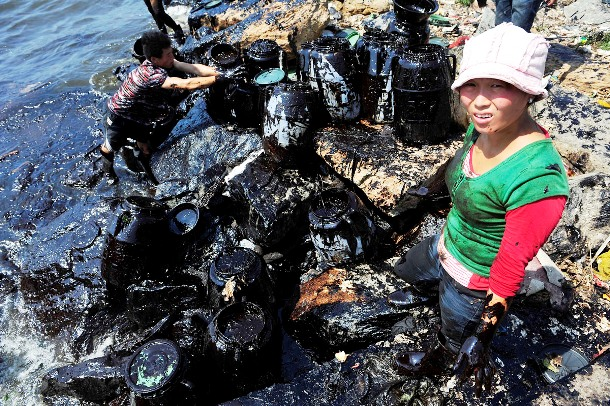 Woman helps to clean up oil at an oil spill site near Dalian Port, Liaoning Province.
