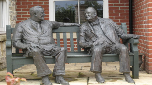 Two statues on a bench