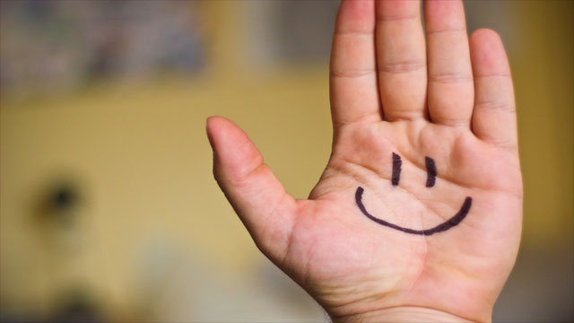 Smiley face on hand