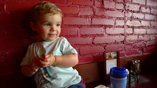 child with crayon next to wall