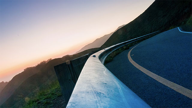 Slow down before the curve, then accelerate through it.