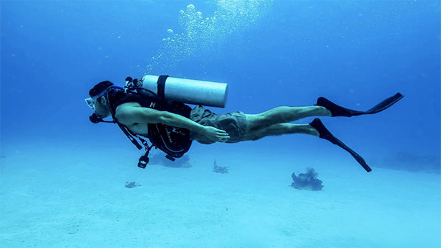 Why do scuba divers fall backwards off of the boat?
