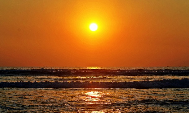 rising sun over water