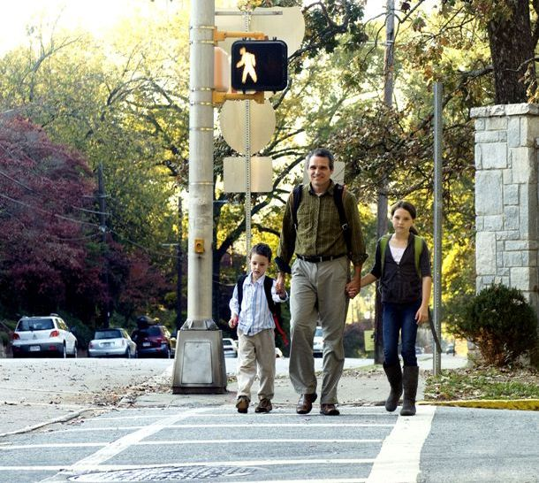Father holding hands with his two young children crossing street