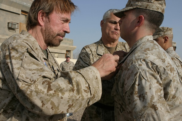 Actor Chuck Norris places corporal chevrons on U.S. Marine Corps Cpl. John Wright