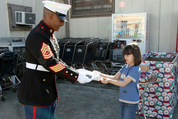 US_Navy_041205-N-1113S-005_A_seven-year-old_gives_an_electronic_toy_game_to_a_Marine_Corps_Gunnery_Sgt