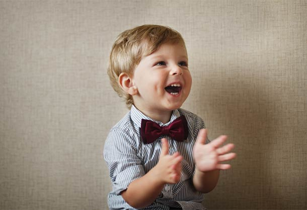 Clapping child with bow tie