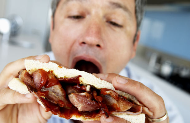 Middle aged man eating a bacon sandwich
