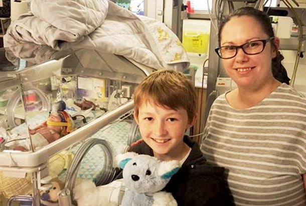 """Campbell """"Bumble"""" Remess stands next to mom with stuffed toy he created"""