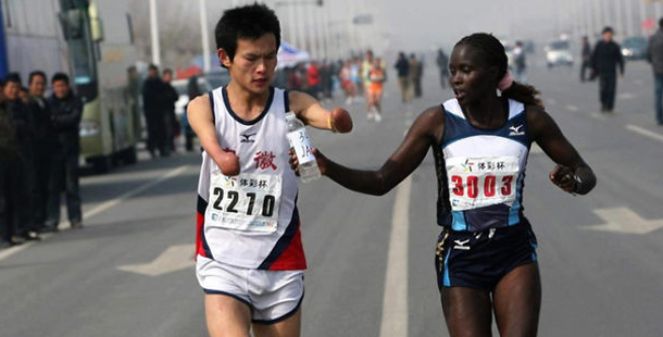 Jacqueline Nytepi Kiplimo helps disabled runner drink water