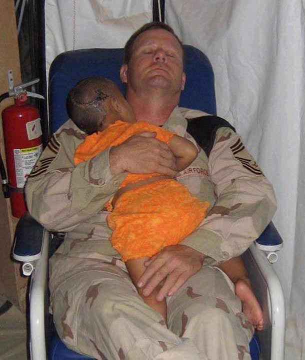 Chief Master Sgt. John Gebhardt comforts little girl who lost most of her family