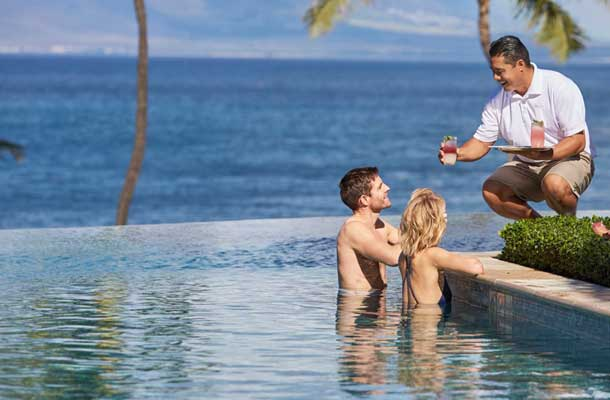 Close up on couple and waiter at Four Seasons pool