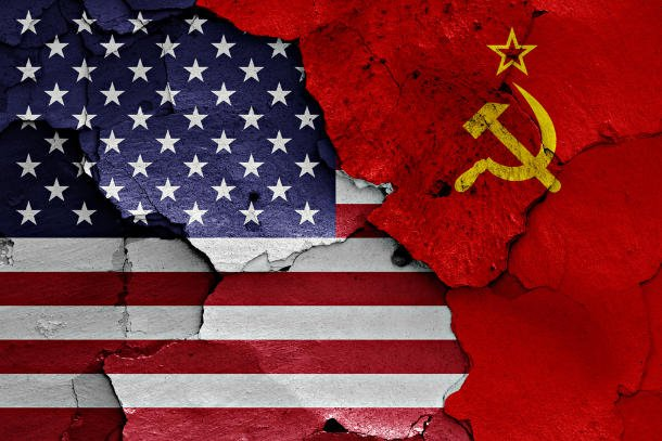 US & soviet union flags together on cracked wall