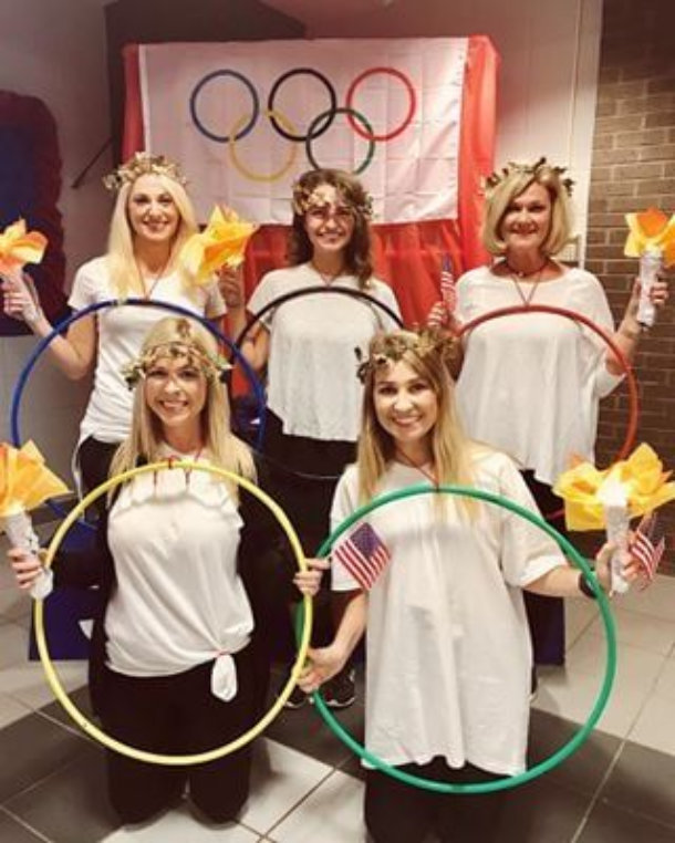 women wearing white shirts holding colored hulahoops to represent the olympic rings