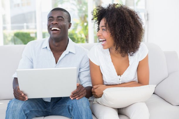 couple laughing at computer