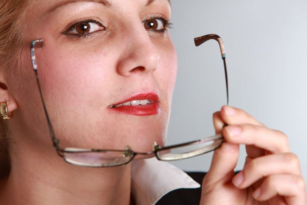woman taking off glasses